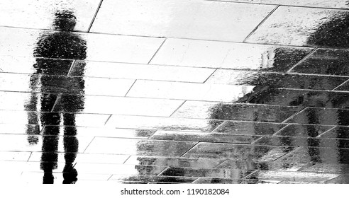 Blurry reflection shadow silhouettes of a man walking on dark rainy city street in black and white