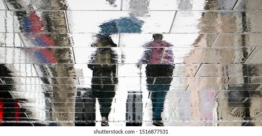 Blurry reflection silhouette on wet city street of two tourist  people walking under umbrella and  pulling traveling suitcases in the rainy autumn day
