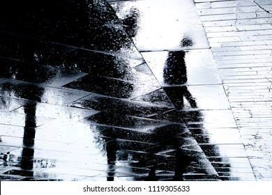 Blurry reflection  silhouette of one person  walking alone  on wet city park sidewalk on a rainy day
