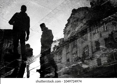 Blurry reflection silhouette of young men walking city streets  in black and white, low angle view with building , in the puddle
