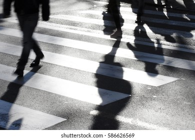 Blurry road crossing with pedestrians making long shadows in the cold, windy and sunny winter in black and white