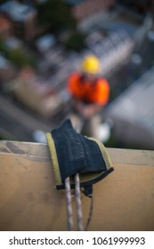 Blurry rope access abseiler back ground abseiling down using static twin ropes against back rope protection, on construction site, Sydney city, Australia