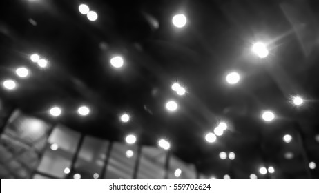 Blurry scene of decorative light bulbs on the ceiling of the hall as abstract background - black and white