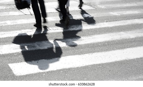 Blurry shadow and silhouette of family with children at zebra crossing