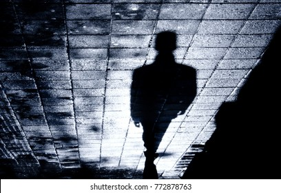 Blurry shadow and silhouette of a man standing  on wet city street sidewalk with water reflections in the night