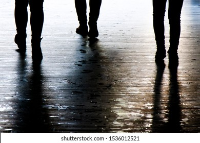 Blurry shadow silhouette of a people walking in the night, detail of legs
