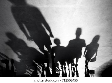 Blurry shadows silhouette of people walking towards the camera on black and white