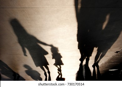Blurry shadows silhouettes of people and a mother with a child  walking on misty summer promenade
