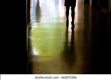 Blurry silhouette and shadow of a woman standing alone, from waist down,  in the alley in the night in city center and a shadow approaching