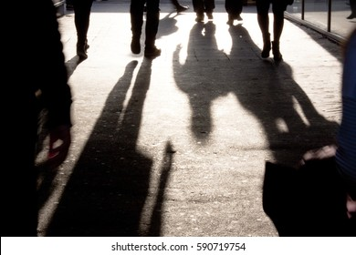 Blurry silhouettes and shadows of people walking on the city sidewalk