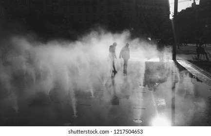 Blurry silhouettes of unrecognizable boy and girl playing in fountain water mist at autumn day. Les Halles square, Paris, France. Black and white photo.