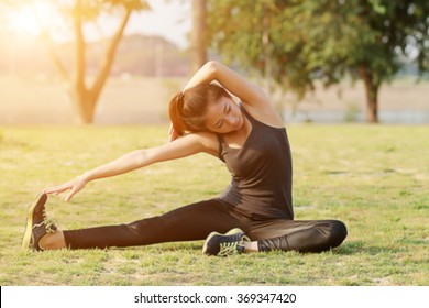 Blurry and soft focus of Athletic woman asian warming up and Young female athlete sitting on an exercising and stretching in a park before Runner outdoor on summer, healthy lifestyle concept