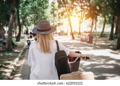 Blurry and Soft Focus Beautiful Hipster Women Walking and Riding Bicycle in the Park - Lifestyle Concept