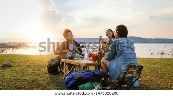 blurry and soft focus of group of Asian friends tourist drinking and playing guitar together with happiness in Summer while having camping near lake at sunset