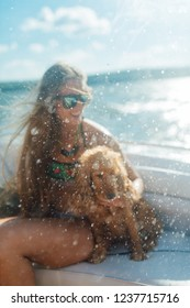 Blurry spray on the background of a girl with long hair and a dog on a boat