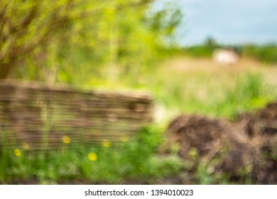 Blurry spring background. Green with wattle fence bokeh. Bright garden wallpaper. Shiny day out of focus. Hollidays in the village. Summertime outdoor backdrop for poster. Summer noon.