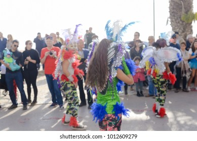 Blurry unrecognizable joyful female performers at the carnival party parade, outdoors background. Back side view having fun hot festive feathers sexual glamor show, traditional sensual beauty clothes