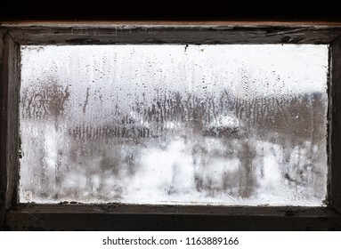 blurry view of russian village through water drops on misted frozen window of rural house in cold winter day (focus on ice surface on the glass)