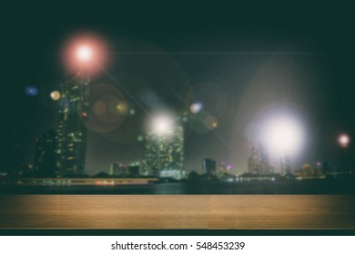 Blurry Vintage tone of Perspective wood and Empty top wooden shelves of asian city of Bangkok , Thailand at night time