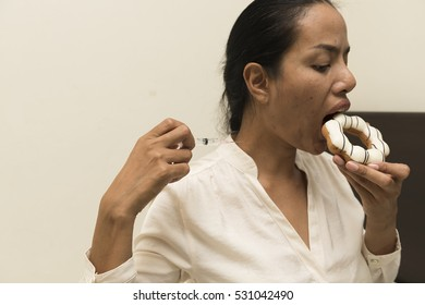 Blurry of women eating donut with syringe on.