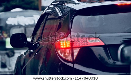 A blurry yellow brake lights of a black car in the street isolated unique photo