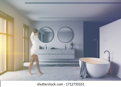 Blurry young woman walking in luxury sunlit bathroom with whie and black walls, concrete floor, comfortable white bathtub and massive double sink with two round mirrors. Toned image