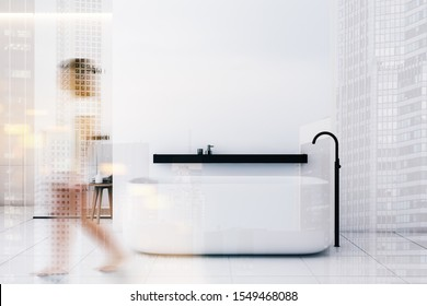 Blurry young woman walking in minimalistic bathroom with white walls, tiled floor, comfortable bathtub and shower stall in background. Toned image double exposure