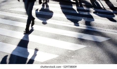 Blurry zebra crossing with  pedestrians making long shadows in the cold, windy and sunny winter in black and white