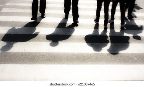 Blurry zebra crossing with  pedestrians silhouettes and  shadows
