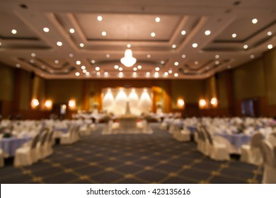 Blur's banquet hall for wedding cakes on the middle of the room and a banquet table on the side.