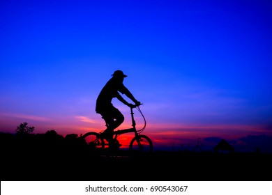 blury bicyclist and Bicycle silhouettes on the dark background of sunsets. ride bicycle on sunset background.