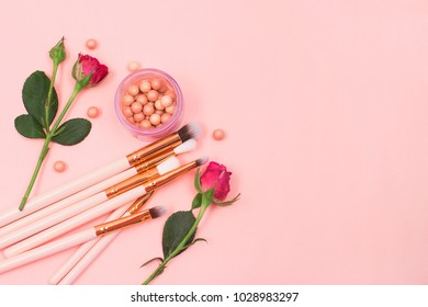 Blush in pearls and make-up brushes on a pink background