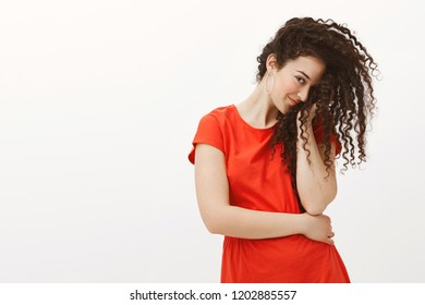 Blushing flirty girlfriend in red dress, covering half of face with curly hair and staring with one eye at camera, smirking, being timid and cute while standing with lowered head over gray wall