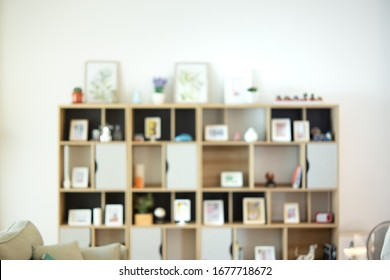 Bluured of wood shelf with picture in the living room. Background concept.