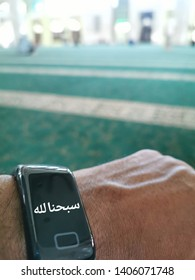 Bluury image of the ineer site of Mosque with smart watch displaying Arabic word praising Allah.