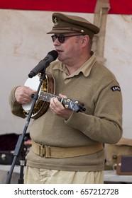 BLYTH, NORTHUMBERLAND, ENGLAND. UK. May 21, 2017.  World War 2 Reenactment at Blyth Battery. Maning in uniform, singing and playing ukulele.    May 21, 2017.  Blyth, Northumberland, England, UK.