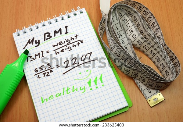 BMI. Measuring tape, a marker and a notepad with a Body mass index formula