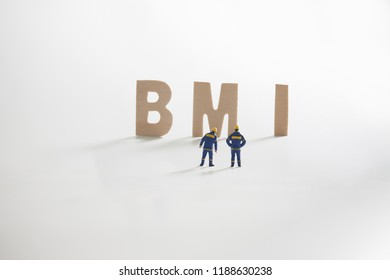 BMI word  with Miniature people: Engineer standing infront use as business concept.