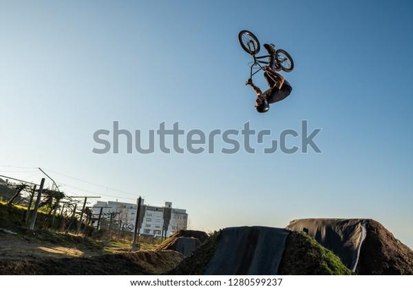 BMX Bike back flip jump on a dirt track.