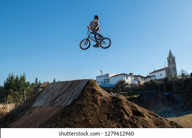 BMX Bike jump over a dirt trail on a dirt track.