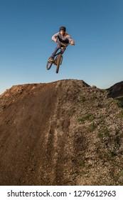 BMX Bike jump over a dirt trail on a dirt track.