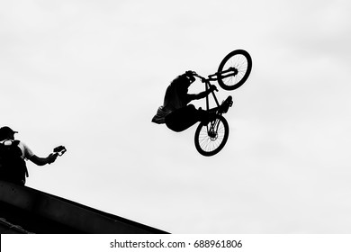 BMX bike jumping in the sky on high speed, black and white silhouette. Extrem Sport