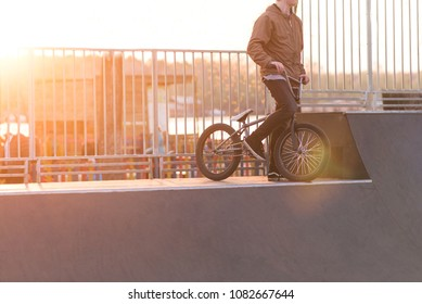 BMX cyclist is standing on a ramp skate park on the background of the sunset. Bmx bicycle and cyclist on the sunset. Copyspace.