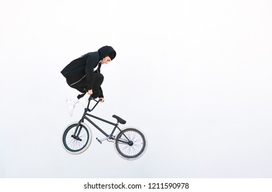 Bmx freestyle on the background of a white wall. BMX rider makes a TAilwhip trick on a white background. Bmx concept