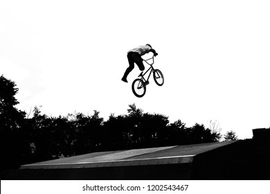 BMX freestyle and stunt riding concept. Professional rider performing various stunts on bike. Monochrome summertime picture of unrecognizable guy riding off-road sport bicycle in skatepark