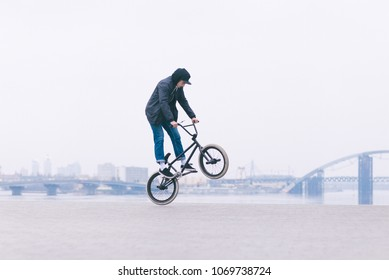 BMX freestyle. Young BMX bicycle makes tricks on the background of a city landscape