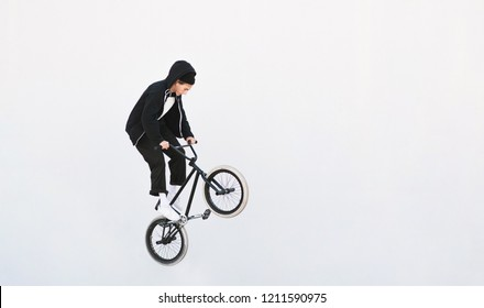 BMX freestyle. Young BMX bicycle makes tricks on the white background. Copyspace7 Bmx trick on a white background