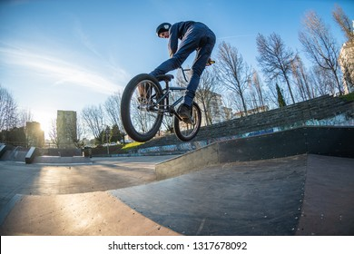BMX jump in a wooden ramp at skate park.