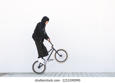 Bmx racer makes a trick in against the background of a white wall. Bmx rider with a bicycle in flight on a white background. Street bmx freestyle