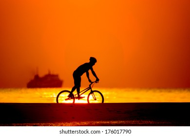 bmx rider action against sunset on the beach.
